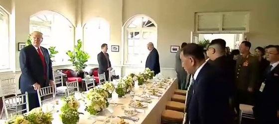역사적 첫 북미정상회담이 열린 12일 오전 싱가포르 센토사 섬 카펠라호텔에서 미국 도널드 트럼프 대통령과 북한 김정은 국무위원장이 업무 오찬을 하기 위해 입장하고 있다. [스트레이츠타임스 홈페이지 캡처=연합뉴스]