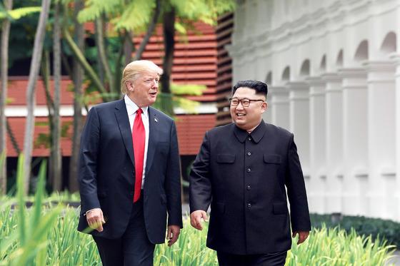 역사적 첫 북미정상회담이 열린 12일 오전 싱가포르 센토사 섬 카펠라호텔에서 미국 도널드 트럼프 대통령과 북한 김정은 국무위원장이 단독회담을 하기 위해 회담장으로 향하고 있다. [싱가포르 통신정보부 제공=연합뉴스]
