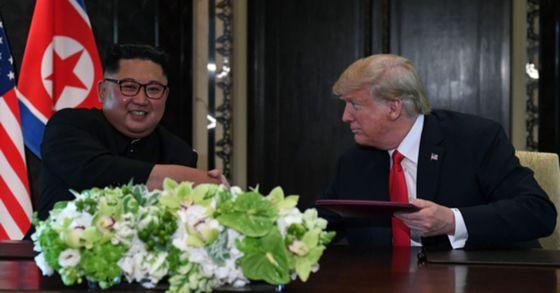 북미정상회담이 열린 12일 오후 싱가포르 센토사 섬 카펠라호텔에서 미국 도널드 트럼프 대통령과 북한 김정은 국무위원장이 공동합의문에 서명하고 있다. [AFP=연합뉴스]
