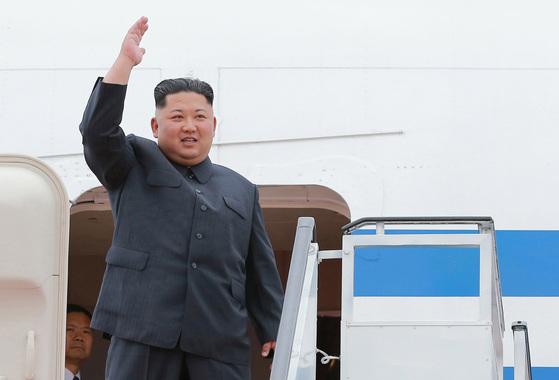 김정은 위원장이 6월10일 평양에서 싱가포르로 향하는 비행기에 오르기전 손을 들어보이고 있다.[EPA=연합뉴스]