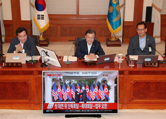 문재인 대통령이 12일 국무회의를 시작하기에 앞서 북미 김정은 북한 국무위원장과 도널드 트럼프 미국 대통령이 만나는 장면의 생중계 화면을 지켜보고 있다. [청와대사진기자단]