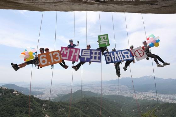 3일 수락산 하강바위에서 '인스타산악회&멀티암벽' 동호인들이 로프에 매달린 채 투표 독려 팻말을 들고 있다. 오종택 기자