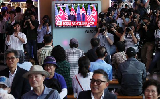 12일 서울역에서 시민들이 싱가포르에서 열린 북미 정상회담 상황을 TV로 시청하고 있다. [연합뉴스]