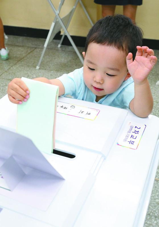 6·13 지방선거 투표일인 13일 오전 서울 여의도중학교에 마련된 여의동 제5투표소에서 한 어린이가 어머니의 투표용지를 투표함에 넣고 있다. [뉴스1]