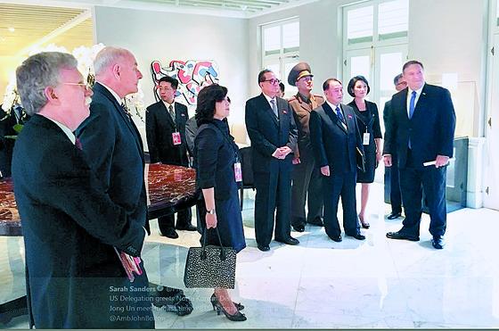 북·미 정상회담 양국 대표단이 12일(현지시간) 싱가포르 카펠라 호텔에서 김정은 북한 국무위원장과 도널드 트럼프 미국 대통령의 악수 장면을 TV로 바라보고 있다. [연합뉴스]