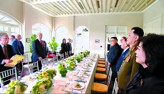 김정은 위원장과 트럼프 대통령이 12일 싱가포르 카펠라 호텔에서 확대정상회담을 마친 뒤 오찬장으로 이동해 자리에 앉기를 기다리고 있다. [AP=연합뉴스]