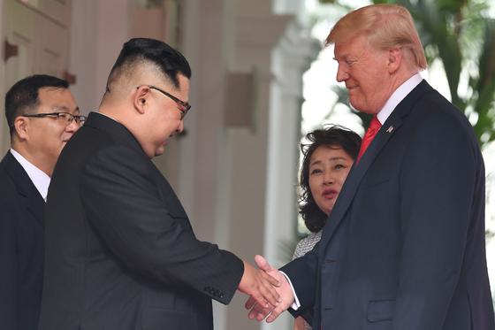 12일 싱가포르에 열린 김정은 북한 국무위원장과 도널드 트럼프 미국 대통령 간 사상 첫 북미 정상회담에 앞서 두 정상이 악수하고 있다. [AFP=연합뉴스]
