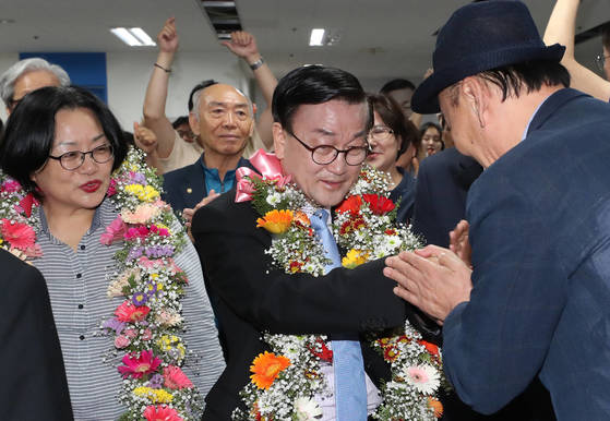 13일 오후 더불어민주당 윤일규 천안병 국회의원 당선인(가운데)이 천안시 선거사무실에서 지지자로부터 꽃다발을 받고 있다. [연합뉴스]