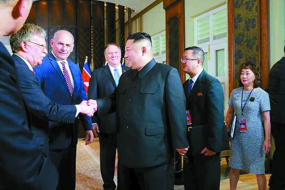 김정은 북한 국무위원장과 존 볼턴 미국 백악관 국가안보보좌관(왼쪽 둘째)이 지난 12일 싱가포르 센토사 섬 카펠라 호텔에서 악수하고 있다. 북한 노동신문은 이 사진을 13일 자에 게재했다. [연합뉴스]