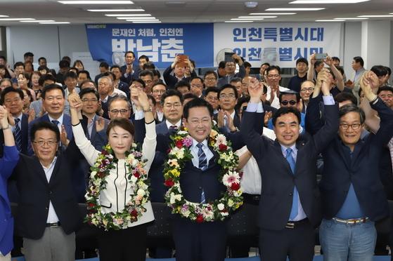 박남춘 인천시장 후보자(앞줄 오른쪽에서 세번째)가 당선 확실하다는 언론보도에 지지자들이 건넨 꽃다발을 목에 걸고 환하게 웃고 있다. [사진 박남춘 후보 캠프 ]