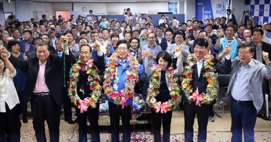 양승조 충남도지사 당선인이 13일 충남 천안시 선거사무실에서 꽃목걸이를 목에 건 채 두 손을 들어보이고 있다. [뉴스1]