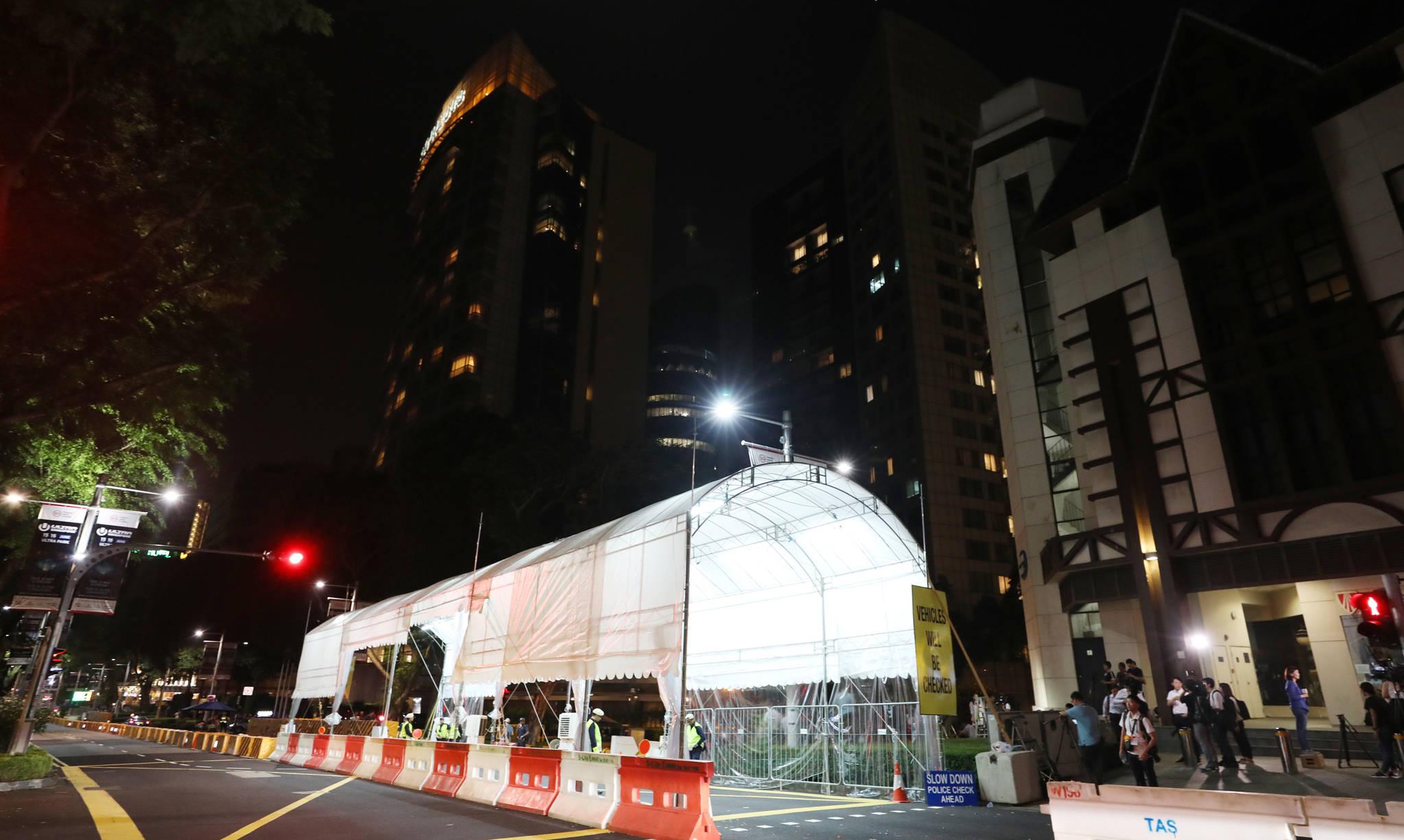 북미정상회담을 이틀 앞둔 10일 밤 김정은 위원장이 묵고 있는 싱가포르 세인트 리지스 호텔 앞에서 경찰이 검문검색을 하고 있다. [연합뉴스]
