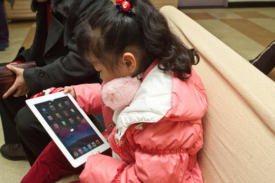 한 어린이가 스마트휴대기기를 유심히 보고 있다. [중앙포토]