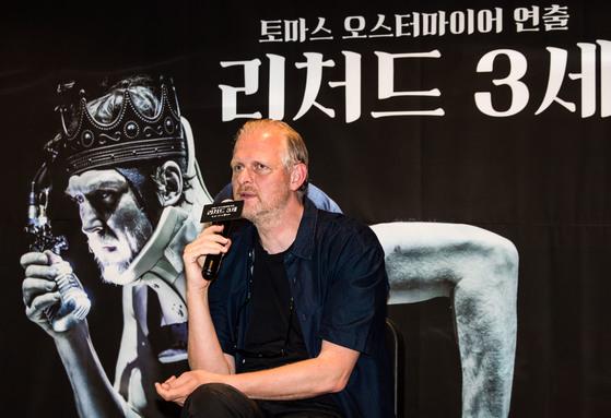 독일 연출가 토마스 오스터마이어가 14일 연극 '리처드 3세' 공연을 앞두고 열린 기자간담회에서 답변하고 있다. 뒤에 보이는 포스터 속 배우는 리처드 3세 역으로 분장한 라르스 아이딩어. [사진 LG아트센터]