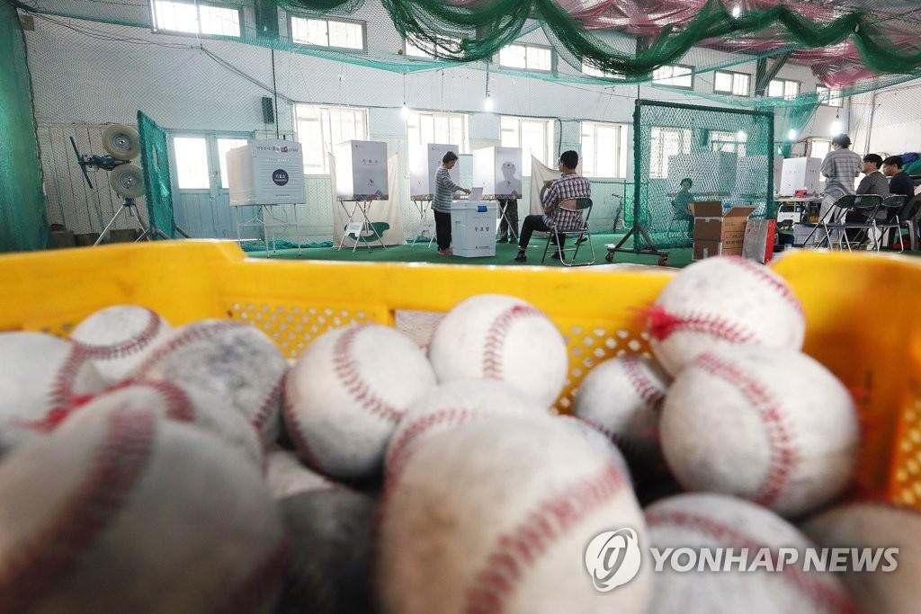 제7회 전국동시 지방선거 투표일인 13일 오전 서울 중구 청구초등학교 야구부 실내훈련장에 마련된 청구동 제1투표소에서 유권자들이 투표를 하고 있다. [연합뉴스]