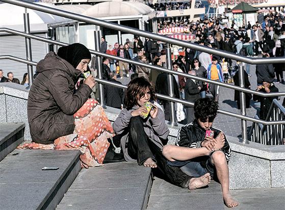 지난 3일 터키 이스탄불에 있는 갈라타 다리 계단 위에서 구걸하고 있는 시리아 난민들. [EPA=연합뉴스]