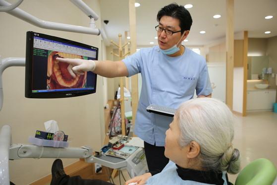 부평 백세플란트치과 박준영 원장이 노인 환자에게 치아 상태를 설명하고 있다. 1일부터 치과의원 노인진료비 부담이 완화됐다.[중앙포토]