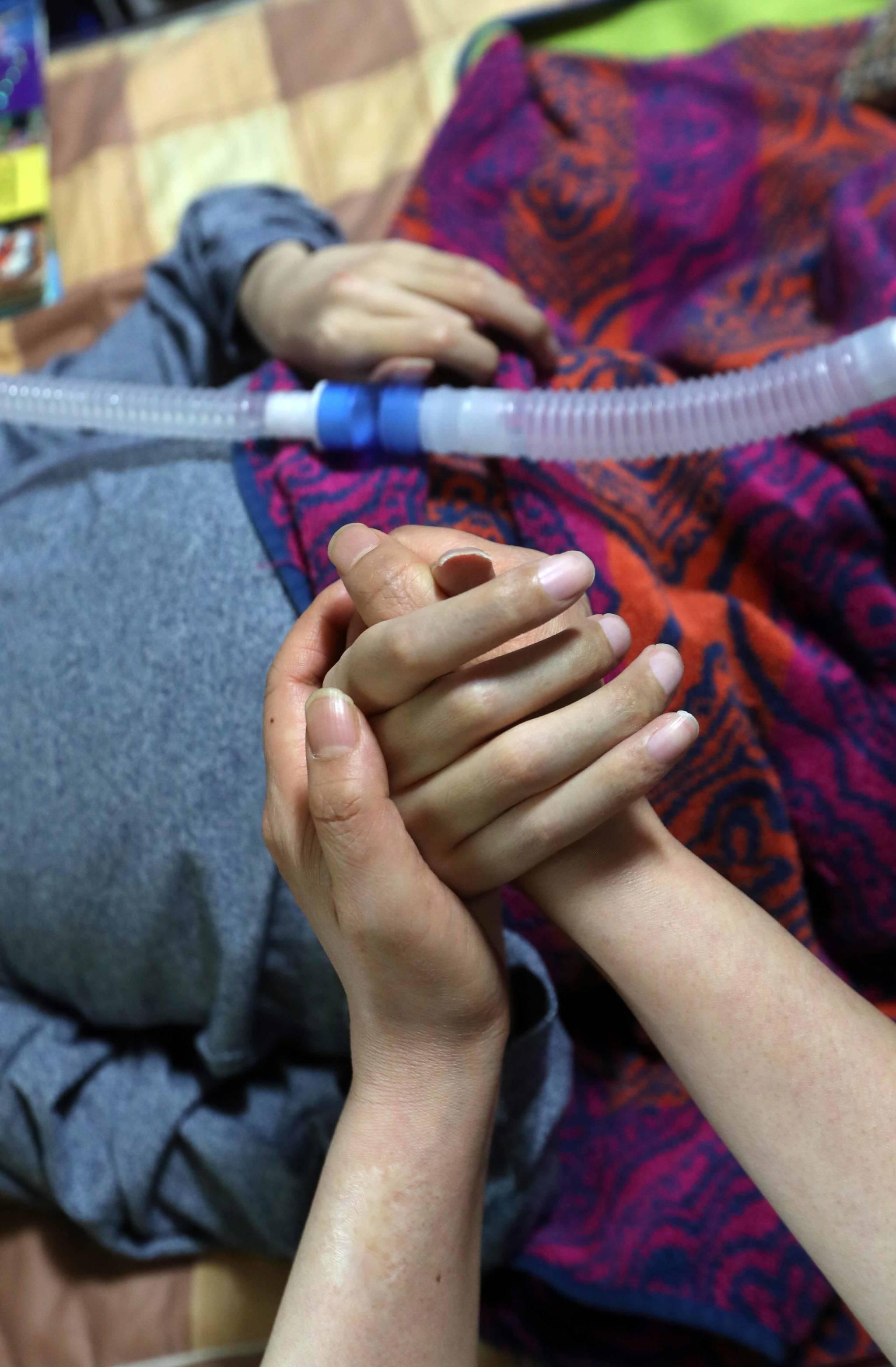 희귀난치성 질환인 뒤센근이영양증을 앓는 김모(26)씨는 하루 종일 집에 누운 채로 인공호흡기를 사용해야 한다. 옆에서 돌보는 가족들도 24시간 눈을 뗄 수가 없다. 김씨의 손을 잡고 있는 어머니의 손. 김상선 기자