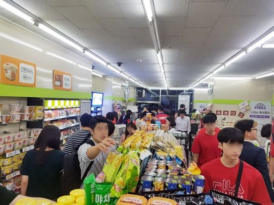 18일 편의점 CU에서 월드컵 거리 응원에 나선 시민들이 제품을 구매하고 있다. [사진 CU]
