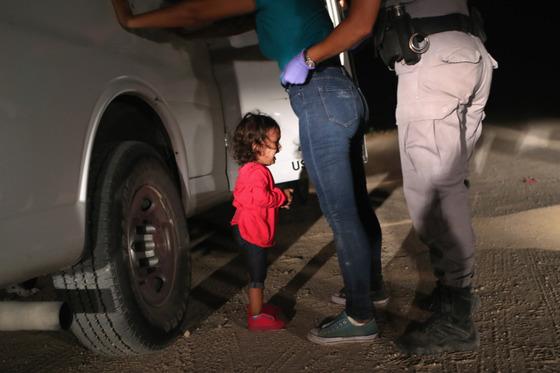 온두라스에서 온 2살배기 소녀가 미 국경순찰대원을 올려다보며 울고 있다. [존 무어]