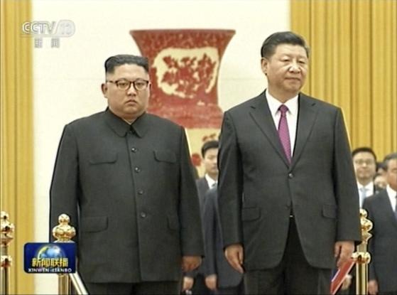 19일 중국을 방문한 김정은 북한 국무위원장(왼쪽)이 시진핑 중국 국가주석과 베이징 인민대회당에서 중국군 의장대 사열을 하고 있다. [중국 CCTV 캡처]