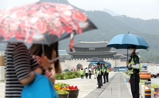오존과 자외선 농도가 전국적으로 나쁨 수준을 보인 지난 8일 오후 서울 종로구 광화문 광장에서 경찰들이 햇볕을 피하기 위해 우산을 쓰고 있다. [뉴시스]