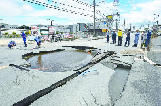 """일본 오사카에서 18일 오전 발생한 진도 6.1 강진으로 다카쓰키시의 도로 하부에 상수도관이 터지면서 물이 고여 있다. 이날 지진으로 오후 2시 30분 기준 4명이 사망하고 300명 이상의 부상자가 발생했다. 외교부는 오사카 지진과 관련, '현재까지 접수된 우리 국민 인명피해는 없다""""고 밝혔다. [지지통신=연합뉴스]"""
