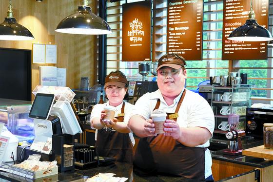 푸르메 재단이 설립한 행복한 베이커리&카페 이혜윤, 김윤우 바리스타가 직접 만든 음료를 내밀고 있다. [사진 SPC]