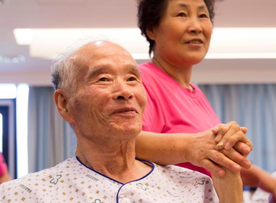 한 요양보호사가 남자 어르신의 손을 잡아주고 있다. [사진 대정요양병원]