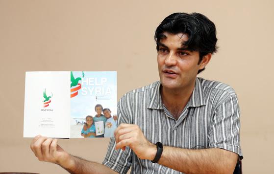 2013년부터 한국에서 시리아 난민·실향민을 돕고 있는 압둘 와합 '헬프시리아' 사무국장이 단체 팸플릿을 들어 보여주고 있다. [변선구 기자]