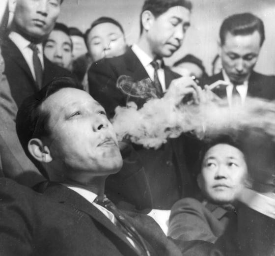 1964년 6월 18일 2차 외유를 떠나기 전 김포공항에서 담배를 피우는 김종필(JP) 전 공화당 의장. 오른쪽은 환송을 나온 오정근 전 최고위원. JP는 63년 10월 1차 외유에서 돌아온 지 불과 8개월 만에 한 · 일 국교정상화 협상에 따른 여론 악화에 책임을 지고 7개월의 2차 외유를 떠났다. 두 차례의 외유 이후 그에게는 '풍운아'라는 수식어가 따라붙게 된다. [사진 김종필 전 총리 비서실]