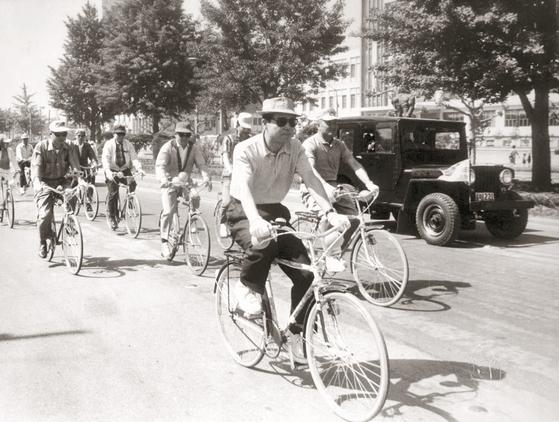 1969년 초여름 김종필 전 공화당 의장(가운데)이 광화문 인근에서 열린 삼천리자전거 신제품 발표 행사에 참석한 뒤 자전거를 시승해보고 있다. [사진 김종필 전 총리 비서실]