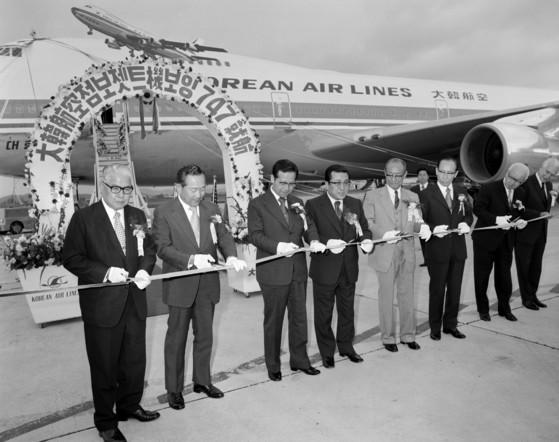 1973년 5월 16일 김포공항에서 열린 대한항공 보잉 747 점보 제트기의 첫 취항식에서 기념테이프를 끊고 있는 김종필 국무총리(왼쪽 셋째)와 조중훈 대한항공 회장(왼쪽 넷째). 맨 왼쪽은 김신 교통부 장관 [사진 김종필 전 총리 비서실]