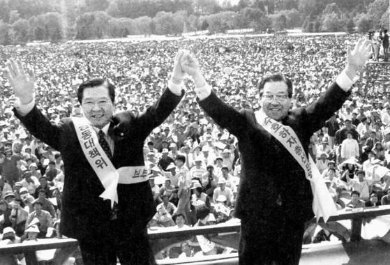 """1996년 5월 26일 서울 보라매공원에서 열린 '4·11 총선 민의수호 결의대회'에 참석한 김대중 국민회의 총재(왼쪽)와 김종필(JP) 자민련 총재가 맞잡은 두 손을 들어 인사하고 있다. 여당의 국회의원 당선자 빼가기에 항의하는 장외집회로 양당 간 공조의 시작이었다. JP는 '김대중 총재는 지난 30년간 나와서 있는 자리는 달랐지만 나름대로 오늘이 있게 한 거목""""이라고 말했다. [사진 김종필 전 총리 비서실]"""