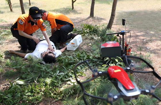25일 오전 강원도 원주에서 KT가 개발한 무인 비행선 '스카이십'과 119 구조대원이 조난자를 응급처치하는 모습을 시연하고 있다. [사진 KT]