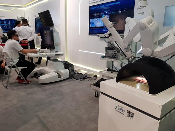 저지연이 거의 없는 5G를 활용해 원격 수술을 진행하고 있는 모습. 왼쪽 책상에 앉은 사람이 손 모양의 장비를 이용해 오른쪽 로봇팔을 조종, 찢어진 피부를 봉합하고 있다. 최현주 기자