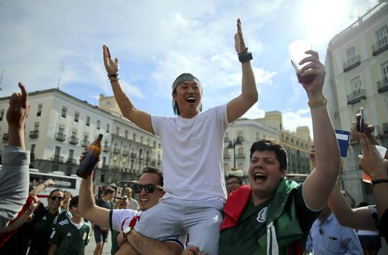 멕시코 축구 팬들이 스페인 마드리드에서 한국 축구 팬을 안고 러시아 월드컵 16강행을 기뻐하고 있다. [AP=연합뉴스]
