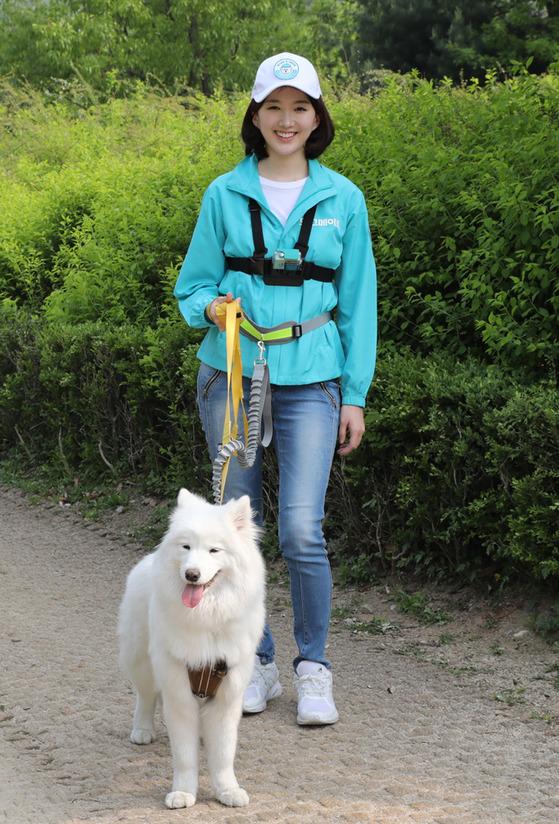 '도그메이트'의 펫시터가 강아지를 산책시키고 있다.