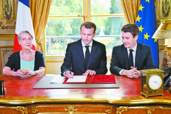 에마뉘엘 마크롱 프랑스 대통령(가운데)이 27일(현지시간) 파리 엘리제 궁에서 철도 개혁안에 서명하고 있다. 왼쪽은 엘리자베스 본 교통 장관, 오른쪽은 벤자맹 그리보 정부 대변인. [AFP=연합뉴스]