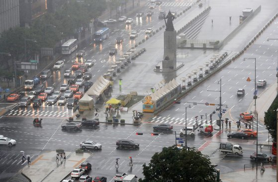 서울을 비롯한 중부지방에 장맛비가 내린 지난 28일 오후 서울 세종대로 네거리에서 우산을 쓴 시민들이 발걸음을 옮기고 있다. [뉴스1]