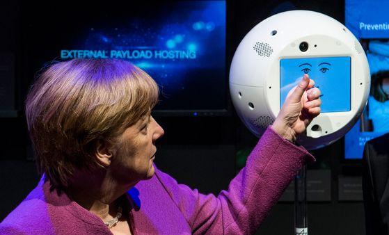 독일 메르켈 총리가 지난 4월 25일 베를린의 한 연구소에서 사이먼과 대화를 나누고 있다. 사이먼은 움직이는 형태로 우주정거장에서 임무를 수행하는 첫 AI로봇이다.[연합뉴스]