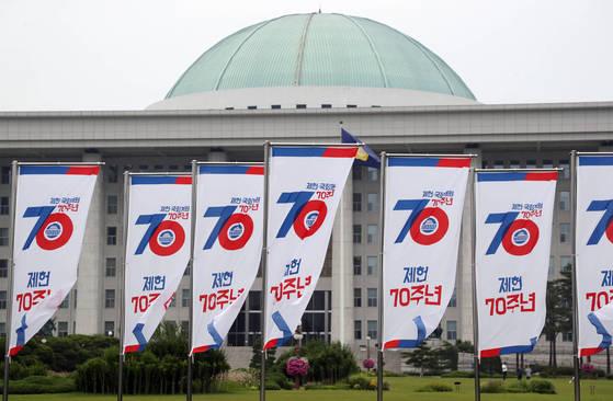 제헌절을 한 달 앞둔 지난 17일 서울 여의도 국회의사당 앞에 제헌 70주년을 기념하는 깃발이 펄럭이고 있다.[연합뉴스]