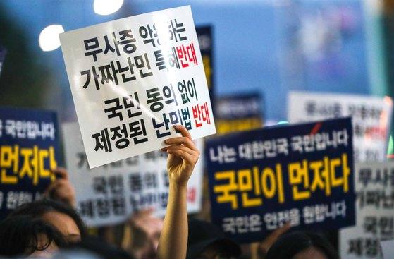 난민 수용을 반대하는 시민들이 지난달 30일 서울 중구 동화면세점 앞에서 난민법과 무비자 제도 폐지를 촉구하고 있다. [뉴스1]