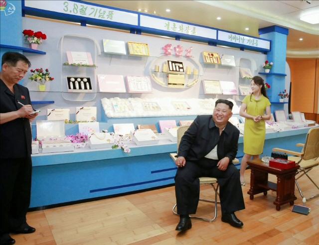 김 위원장이 인민복 속에 입은 흰색 티셔츠가 보이는 채로 편안한 자세로 앉아 활짝 웃고 있는 모습 [사진 연합뉴스]