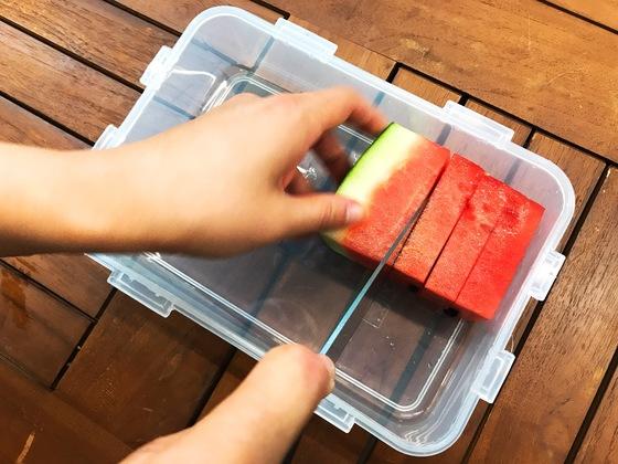 보관할 밀폐용기 그릇 높이에 맞춰 수박 조각을 넣고 식빵을 자르듯 칼로 툭툭 자른다.