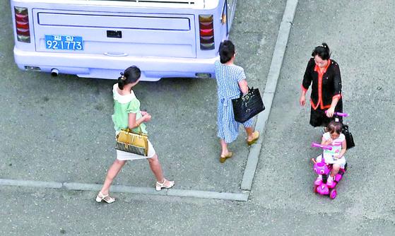 5일 오전 평양에서 출근하는 여성과 아이를 돌보는 엄마가 거리를 지나가고 있다. [사진공동취재단]