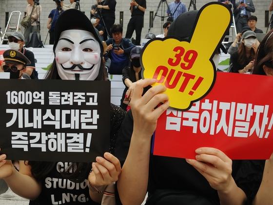 6일 서울 광화문에서 열린 '아시아나항공 경영진 규탄 문화제'에 참가한 금호아시아나그룹 직원들. '가이포크스' 가면을 쓴 참가자들이 '39아웃''침묵하지 말자' 등의 팻말을 들고 있다. 김정연 기자