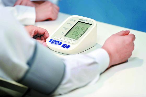 최근연구에서 혈압을 120까지 낮추는것이 합병증 등 발병 위험 낮추는 것으로 나왔다. 서울 신촌 세브란스병원에서 한 고혈압환자가 혈압을 재고 있다. [김상선 기자]
