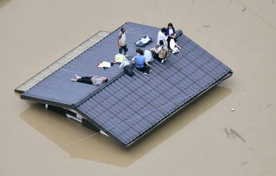 일본 서부 지역에서 기록적인 폭우가 나흘 째 이어진 가운데, 7일 오카야마현 구라시키시에서 침수된 주택 지붕 위에 시민들이 대피해 있다. [AP=연합뉴스]