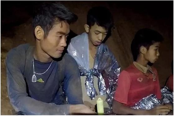 동굴 안에 아이들과 함께 남은 엑까뽄 코치의 모습(왼쪽). [사진 태국 해군 페이스북]
